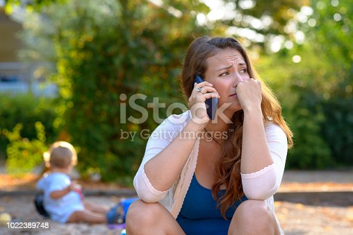Stressed depressed young mother talking on a mobile phone as she sits outside in a playground with her baby son playing behind her