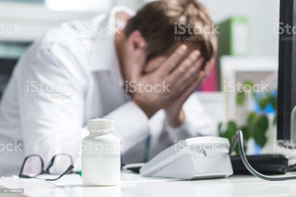 Destacó el doctor cubre rostro bajo presión. Enfermera triste, cansado médico o malestar doc. Medic llorando en oficina del hospital. - foto de stock