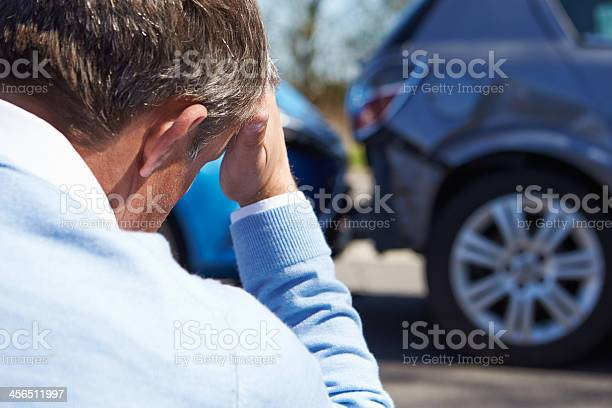Stressed Driver Sitting At Roadside After Traffic Accident Stock Photo - Download Image Now
