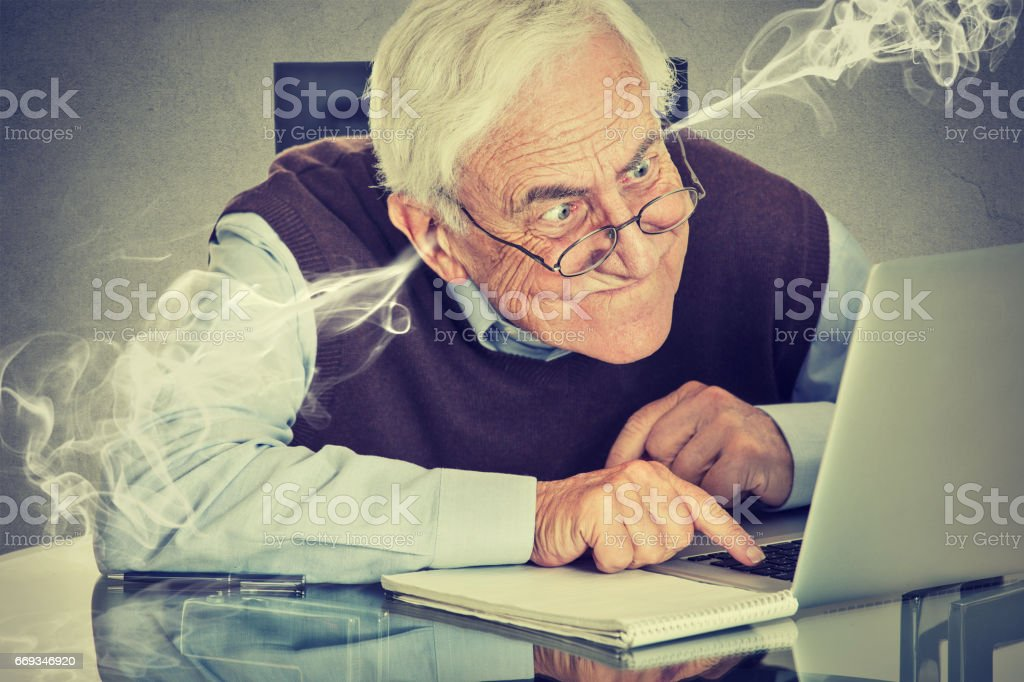 Stressed elderly old man using computer blowing steam from ears stock photo