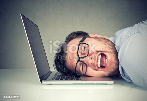 857213750istockphoto Stressed employee man sitting at desk with head on laptop feeling overworked and desperate 960300522