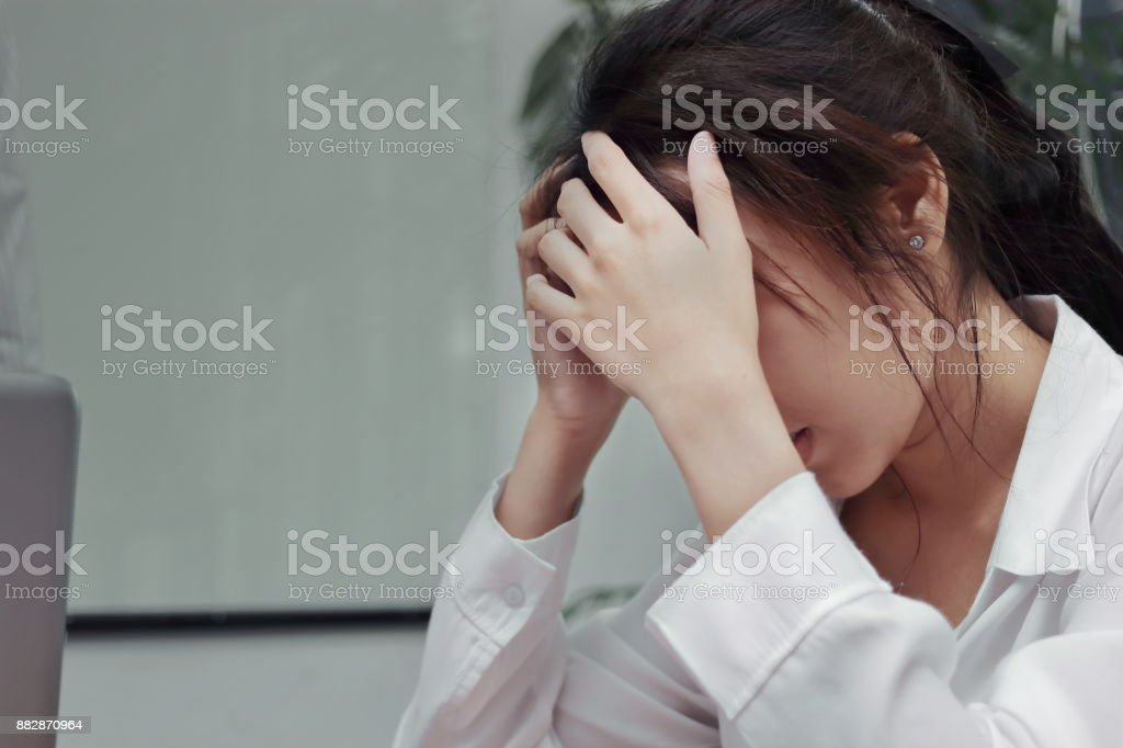 Stressed exhausted young Asian business woman suffering from severe depression in office. stock photo
