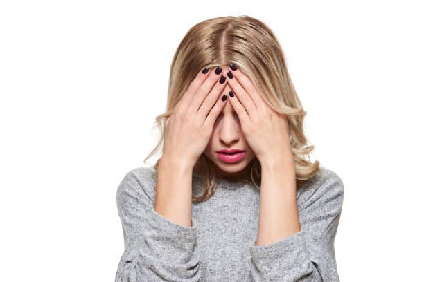 Betonte erschöpft junge Studentin mit starken Spannungskopfschmerzen. Gefühl von Druck und Stress. Deprimiert Schüler mit Kopf in Händen Over White Background. – Foto