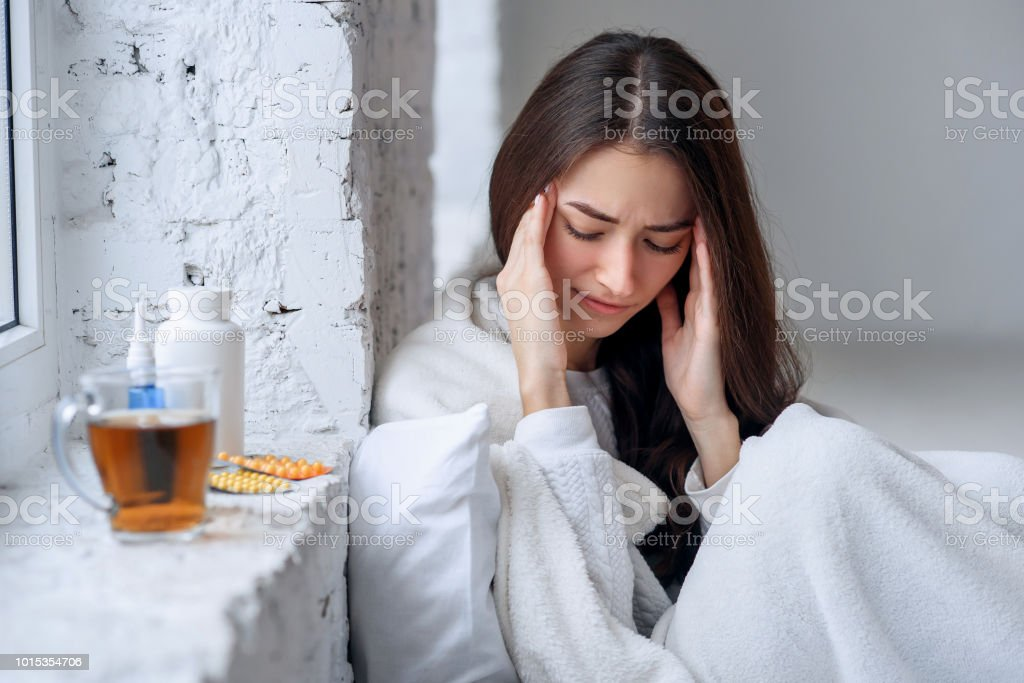 Cold and pain. Stressed exhausted young woman feeling strong head...