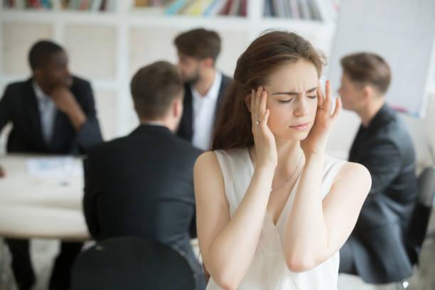 ブリーフィング中に片頭痛を持つ女性会社員を強調しました。 ストックフォト