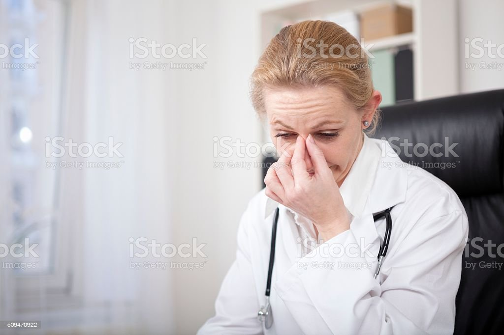 Stressed Female Doctor Holding her Nose Bridge stock photo