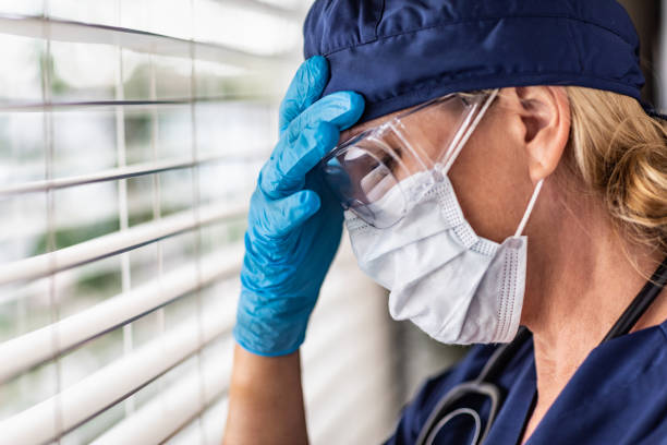 Stressed Female Doctor or Nurse On Break At Window Wearing Medical Face Mask and Goggles stock photo