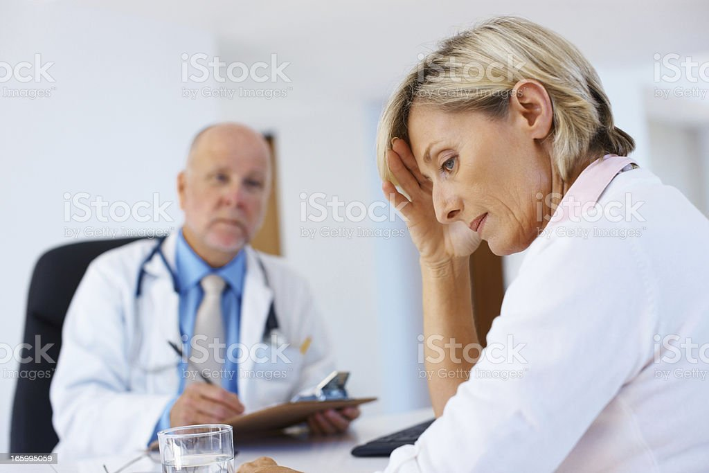 Stressed female patient in clinic with the doctor royalty-free stock photo