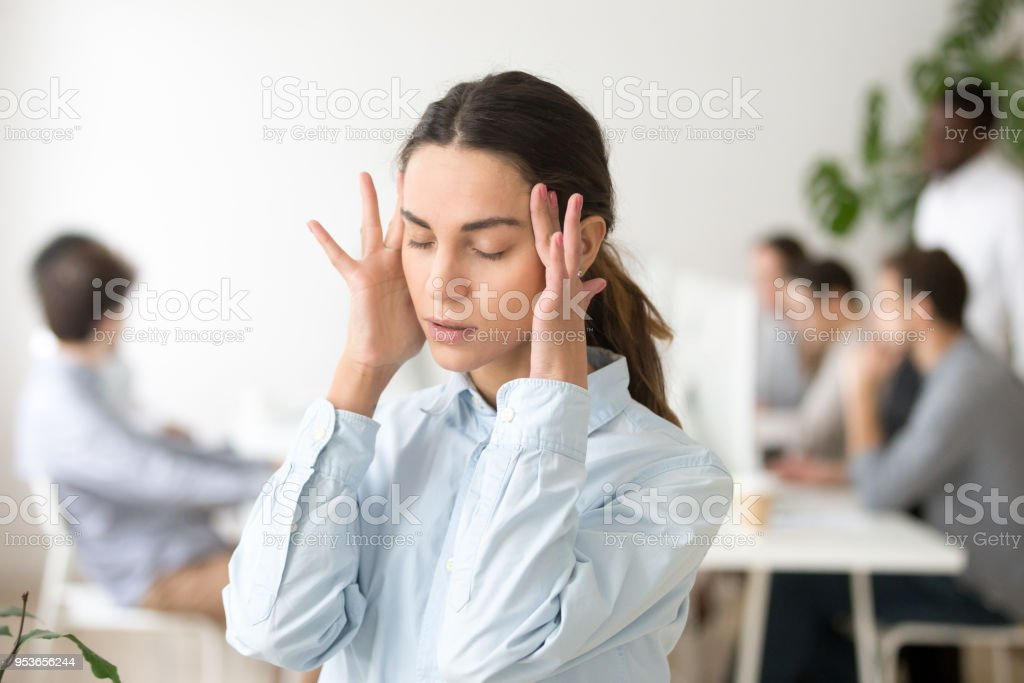 Stressed frustrated young woman employee feeling dizzy or having headache stock photo