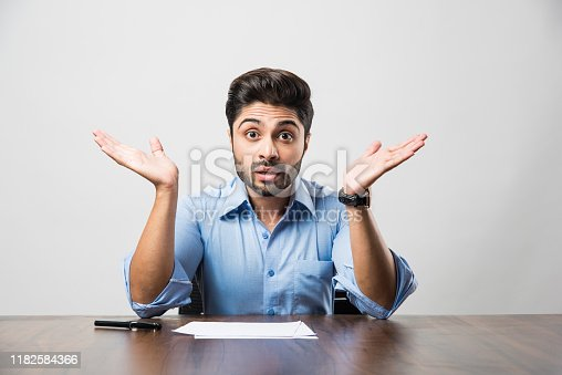 istock Stressed Indian Businessman having headache or Migraine pain while working at office table 1182584366