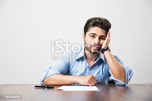 istock Stressed Indian Businessman having headache or Migraine pain while working at office table 1182594032