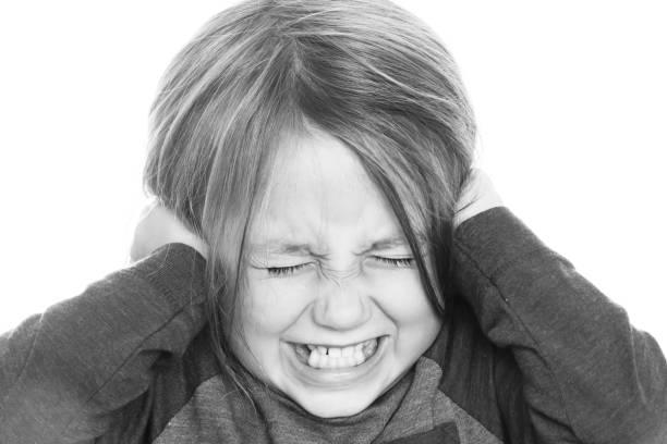 gestresstes kleines mädchen, das ihre ohren mit ihren händen bedeckt - autismus stock-fotos und bilder