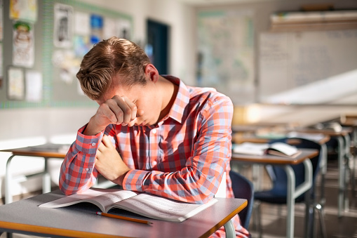 Stressed male student sitting with book at desk. Teenage boy is studying alone in classroom. He is at high school.
