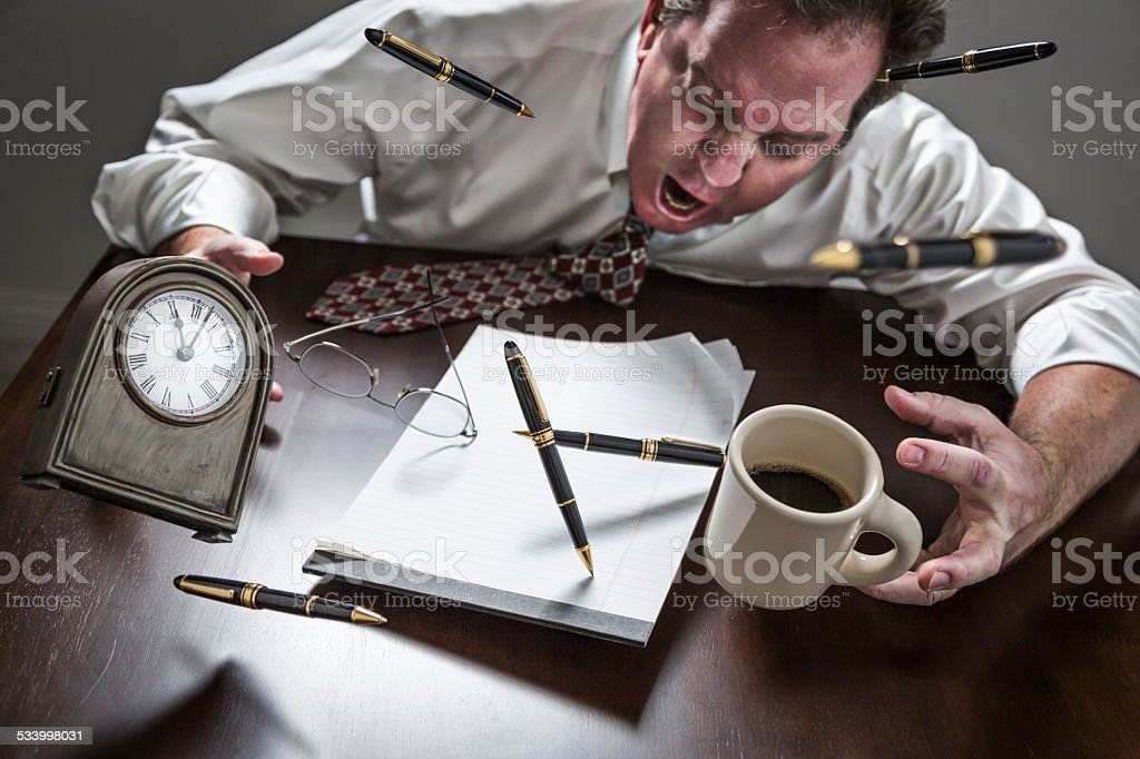 Stressed Man At Desk, Pens, Coffee, Glasses, Clock Flying Up stock photo
