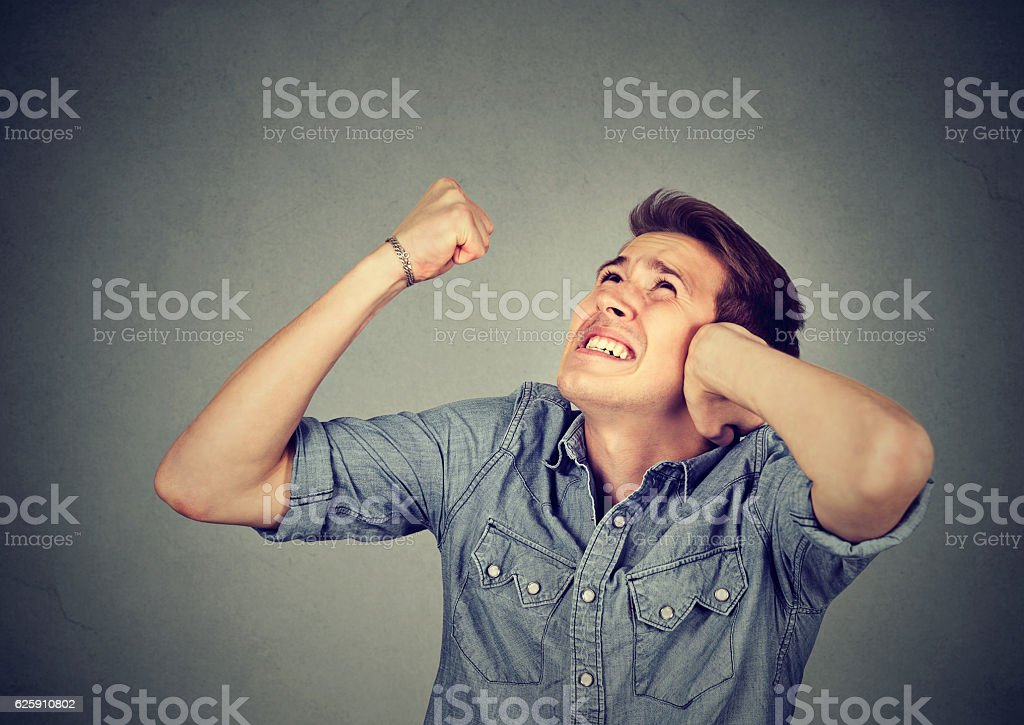 Stressed man covering ears having headache looking up stock photo