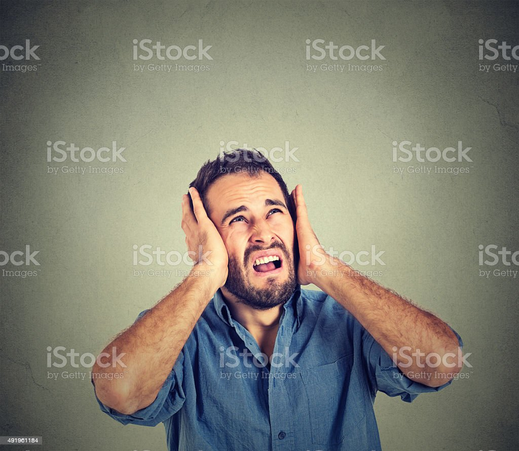 stressed man covering ears, looking up, stop making noise stock photo