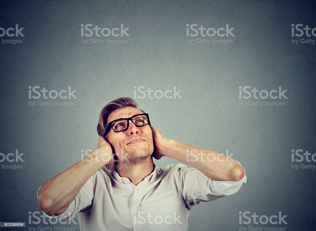 stressed man covering ears looking up stop noise stock photo