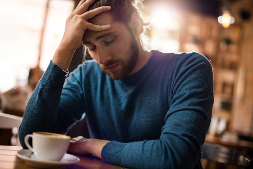 istock Stressed man holding his head in pain in a cafe. 538659042