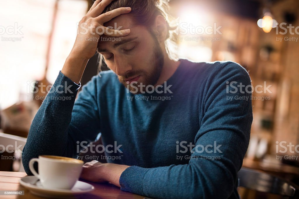 Stressed man holding his head in pain in a cafe. stock photo