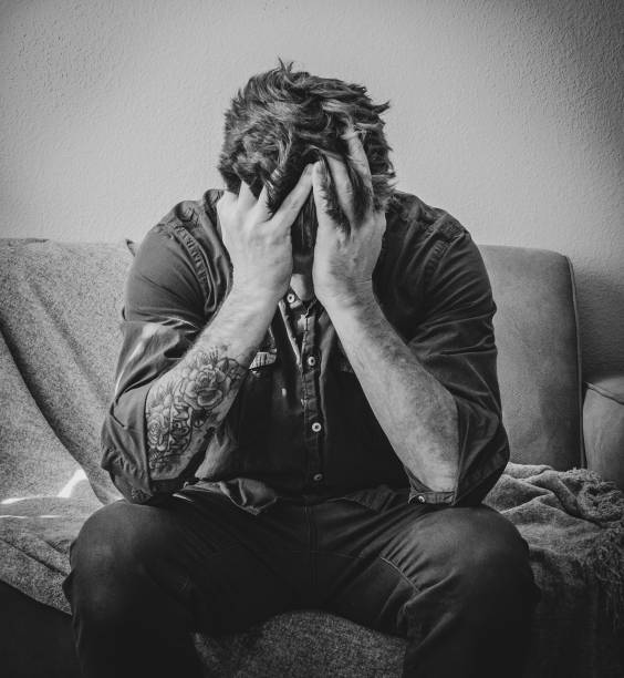 Stressed Man Holds Face in Hands A depressed, stressed out man sits on a couch holding face and head in his hands. post traumatic stress disorder stock pictures, royalty-free photos & images
