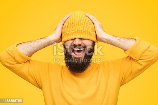 Bearded male in hat keeping hands on head and shouting while standing on bright yellow background