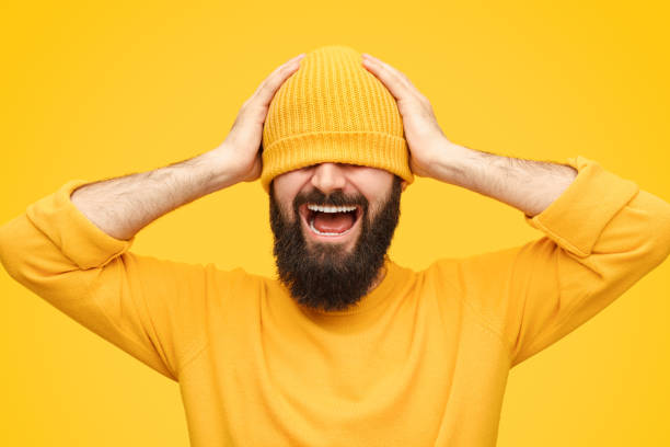 Stressed man in hat screaming Bearded male in hat keeping hands on head and shouting while standing on bright yellow background disillusioned stock pictures, royalty-free photos & images