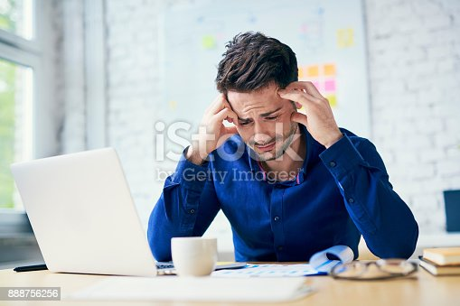 istock Stressed man in office looking on documents 888756256