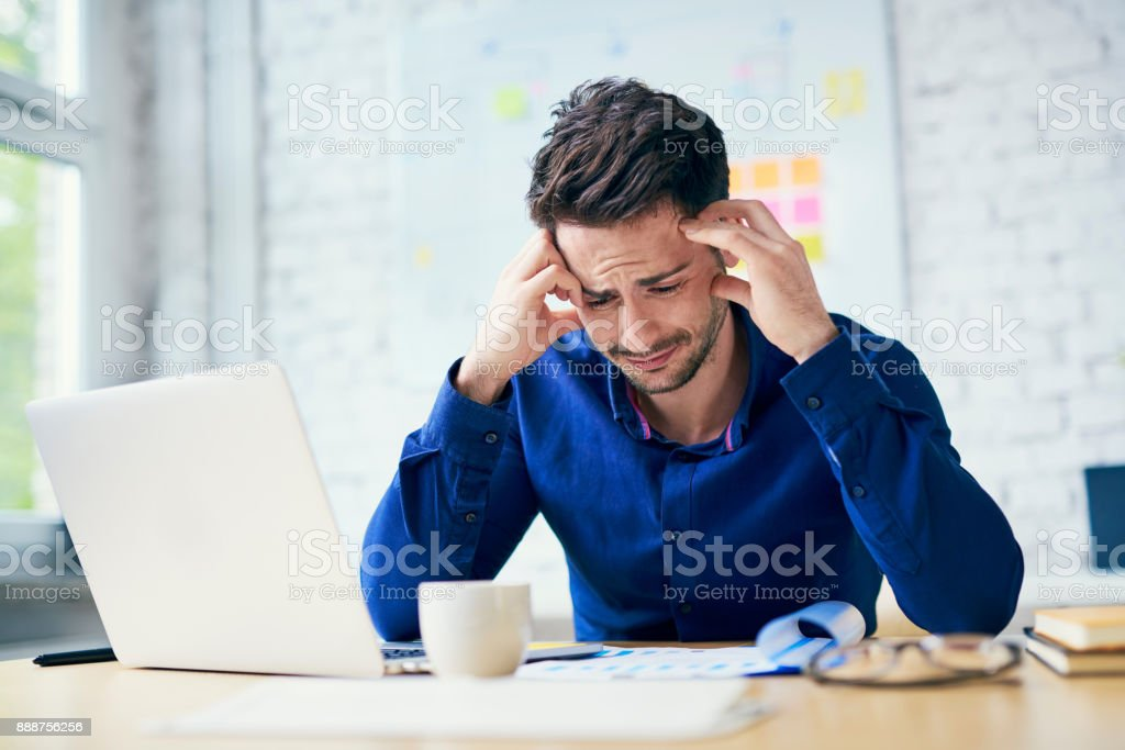 Stressed man in office looking on documents stock photo