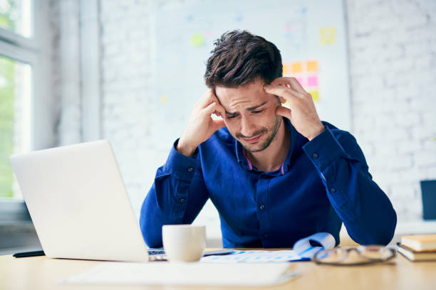 Stressed man in office looking on documents Stressed man in office looking on documents nettle stock pictures, royalty-free photos & images
