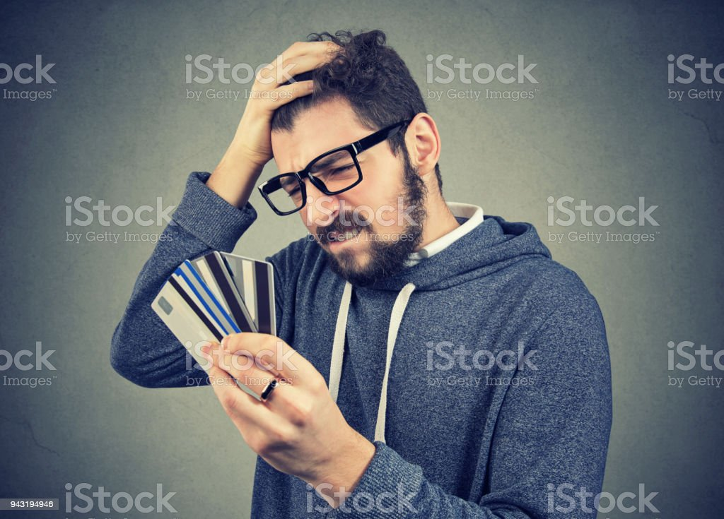 stressed man looking at too many credit cards stock photo