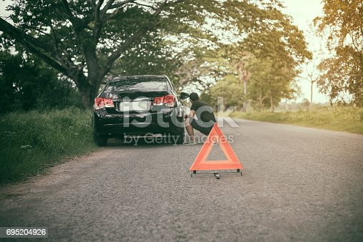 istock Stressed man sitting after a car breakdown with Red triangle of a car on the road 695204926