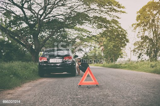 istock Stressed man sitting after a car breakdown with Red triangle of a car on the road 695207014