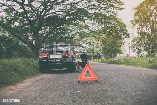 istock Stressed man sitting after a car breakdown with Red triangle of a car on the road 695207556