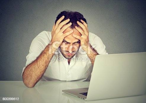 istock Stressed man sitting at his desk in front of computer 600399512