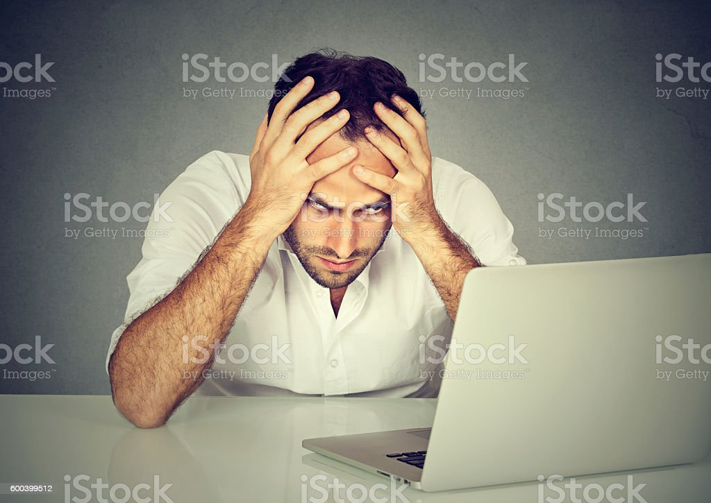 Stressed man sitting at his desk in front of computer stock photo