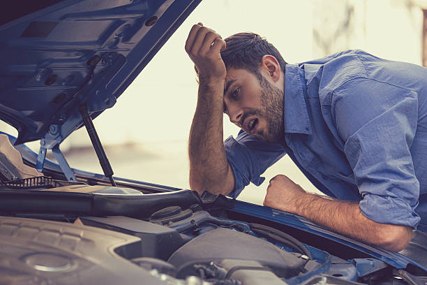 stressed man with broken car looking at failed engine - impaired driving stock photos and pictures