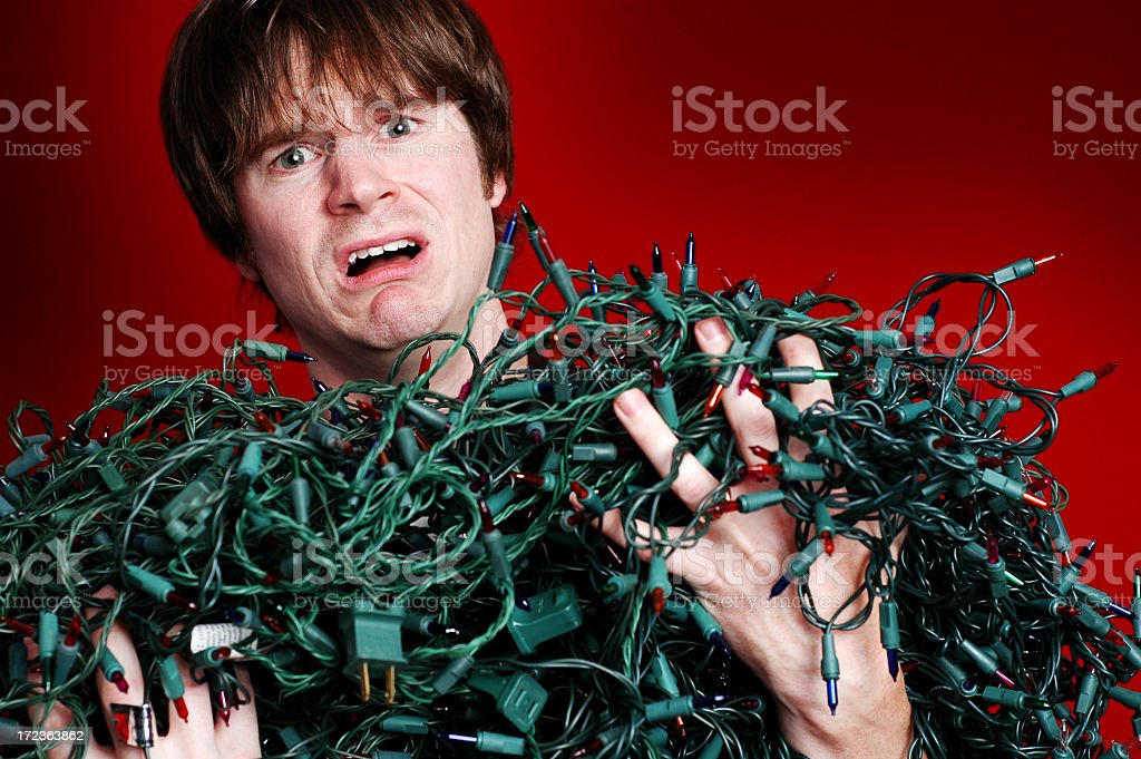 Stressed Man with Bunch of Tangled Christmas Lights royalty-free stock photo