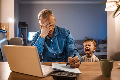 Busy mature businessman working from home and watching his crying son at night, who is is yelling at him. Upset displaced father forced to work from home as the pandemic corona virus (COVID-19) forces many employees to work from home. Real people. Copy space.