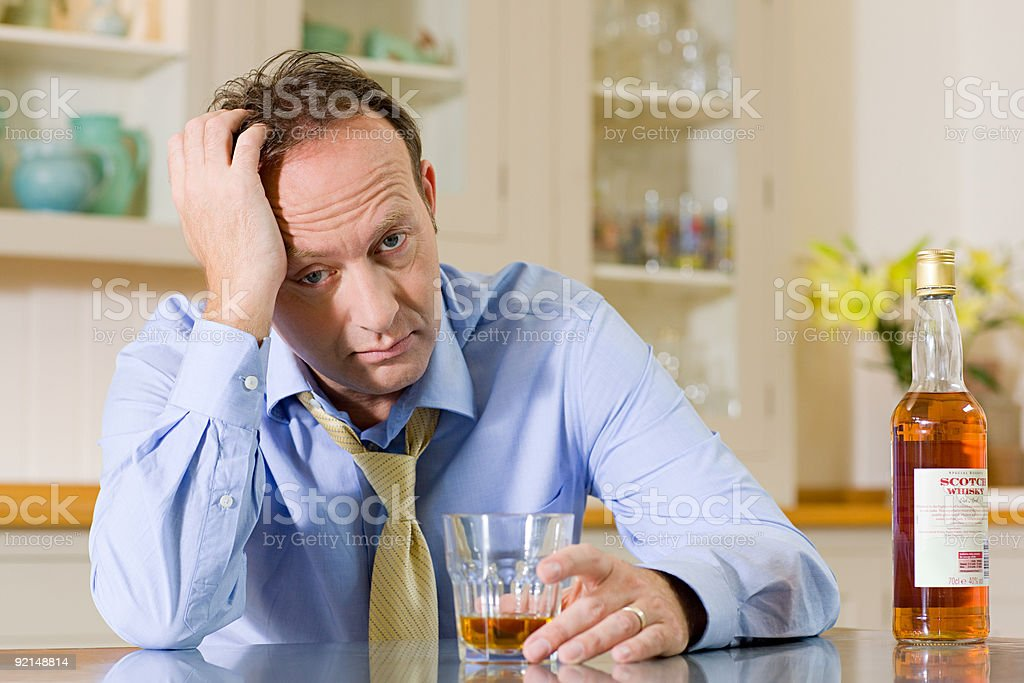 Stressed man with whisky stock photo