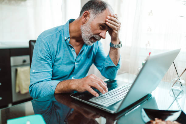 Stressed man working from home and using laptop stock photo