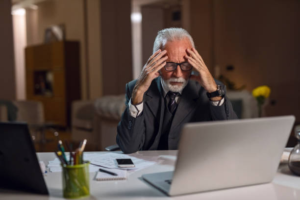 Stressed mature businessman having headache while working on laptop in the office. stock photo