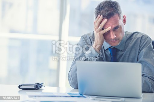 istock Stressed mature businessman with laptop. 865527674