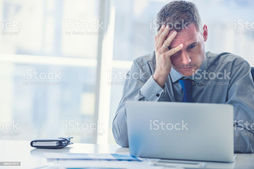 Stressed mature businessman with laptop. stock photo