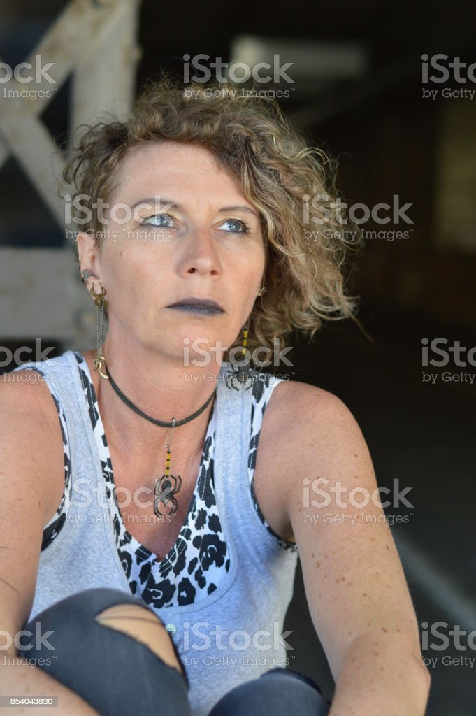 stressed mature punk lady looking thoughtfully above stock photo