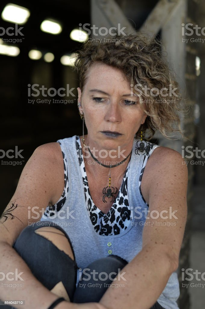 stressed mature punk lady looking thoughtfully down stock photo