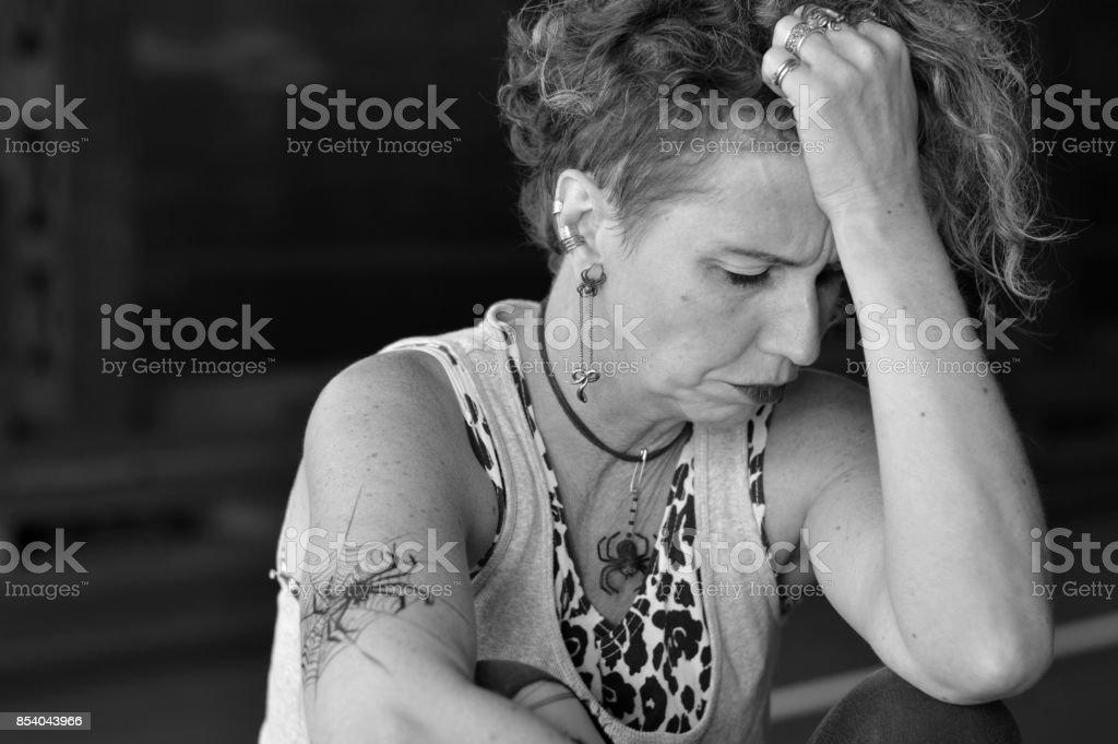 stressed mature punk woman lost under a bridge stock photo