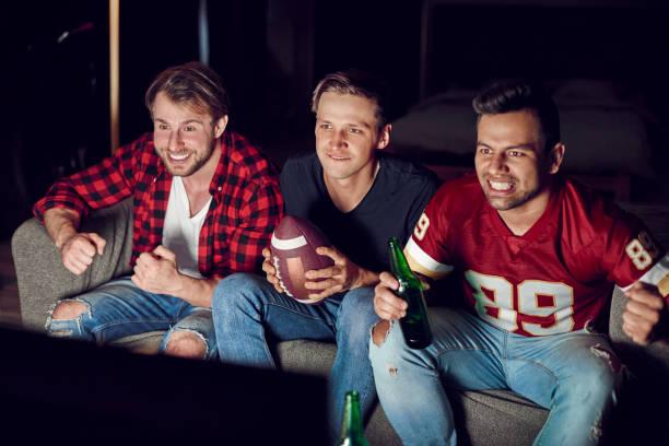 benadrukt dat mannen kijken wedstrijd in concentratie - football friends tv night stockfoto's en -beelden