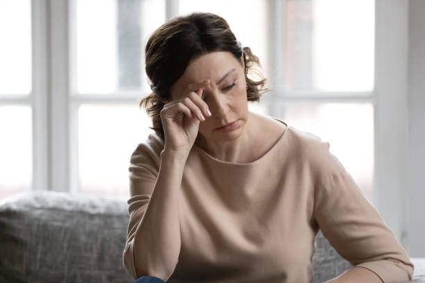 Stressed middle aged woman worrying about hard life situation. stock photo