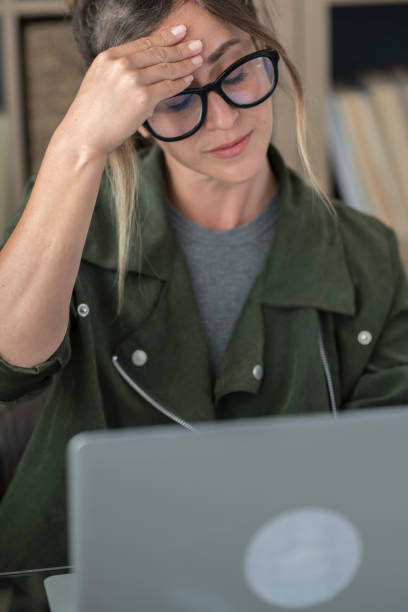 Stressed millennial Caucasian woman with headache look at laptop screen work online from home office. Tired young female use computer browse internet on device. Technology concept. stock photo
