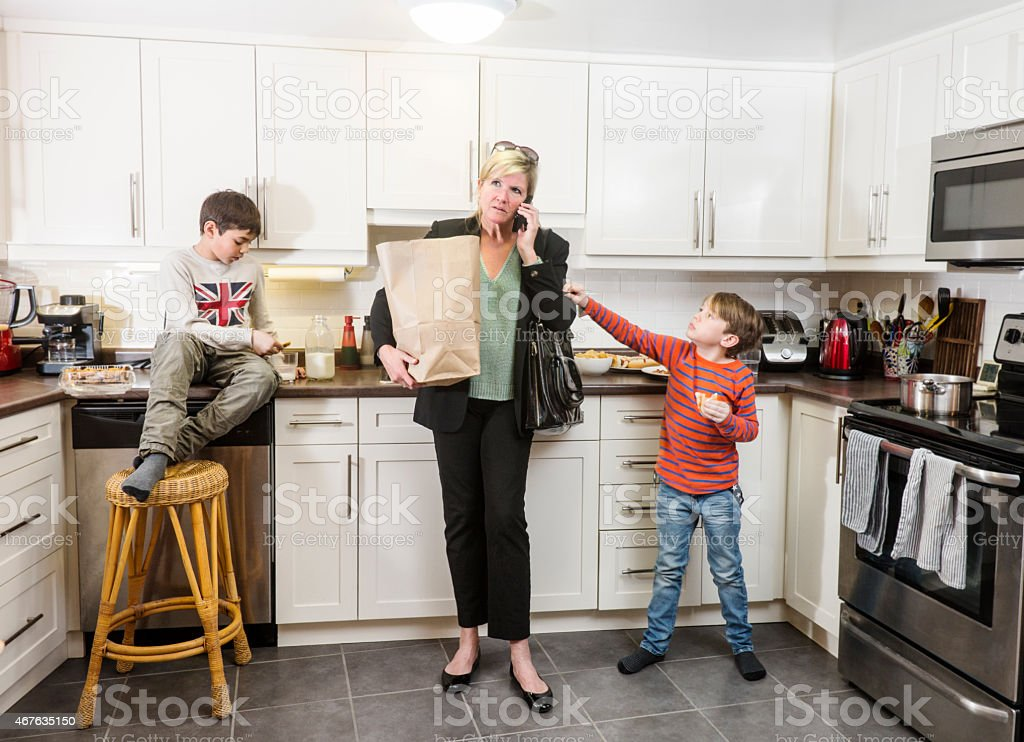 Stressed mother and businesswoman arriving home to her family stock photo